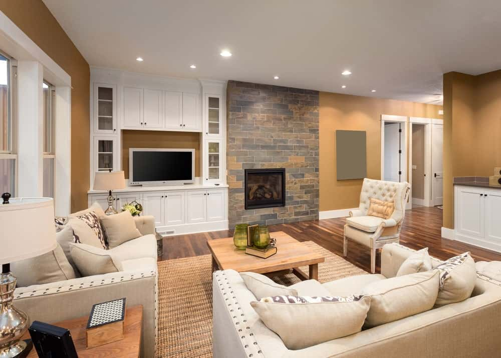 This living room showcases beige seats and a wooden coffee table over a woven rug. It includes a flat-screen TV next to the fireplace illuminated by recessed ceiling lights.