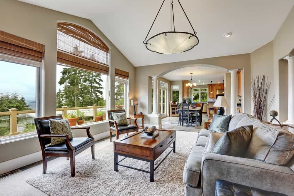 Bright living room with layered rugs and picture windows overlooking the outdoor scenery. It is illuminated by a large pendant light that hung over the wooden coffee table surrounded with a gray sofa and black leather armchairs.