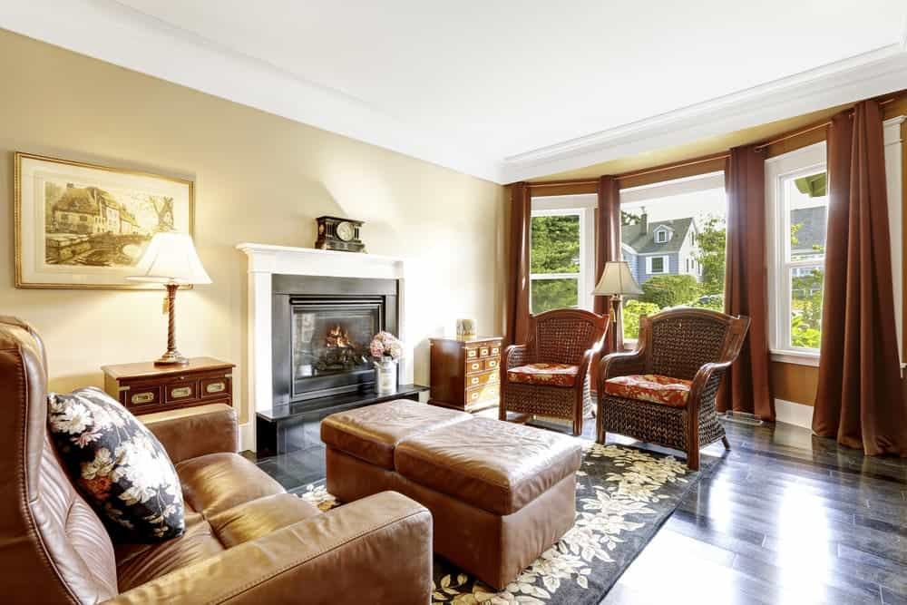 The medium-sized living room features wicker and brown leather armchairs paired with a matching ottoman that sits on a black area rug. It has a fireplace and white framed windows covered in red draperies.