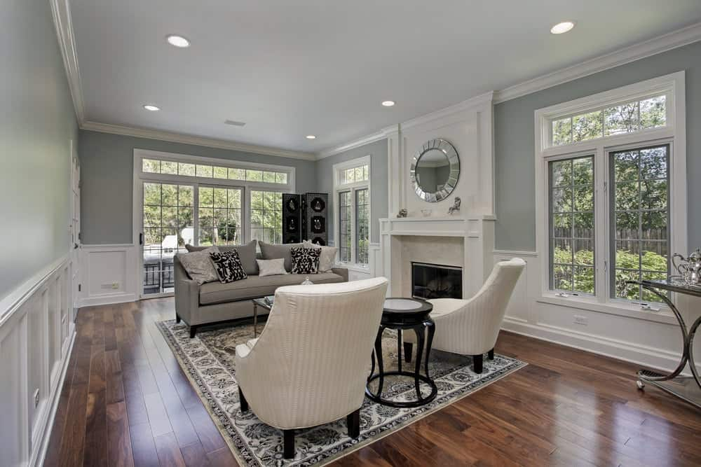 Gray living room decorated with a round chrome mirror mounted above the fireplace topped with mini sculptures. It has a gray sofa and white striped chairs with a black side table in the middle.