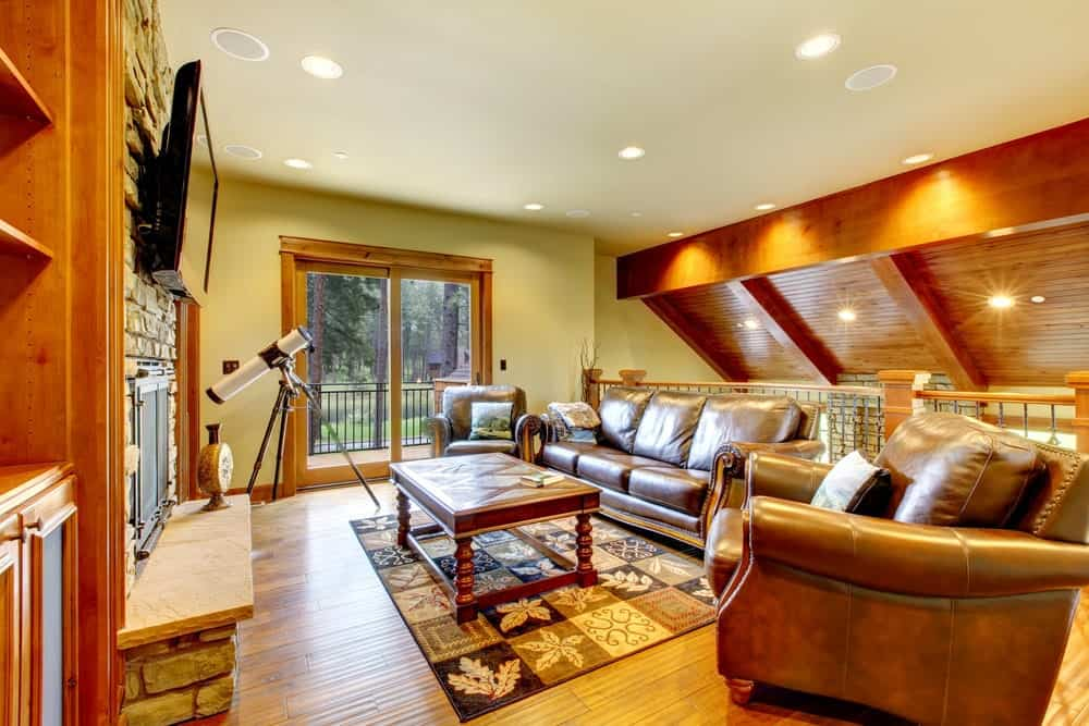 The cozy living room showcases leather seats and a wooden coffee table over a checkered area rug. It faces the fireplace and TV mounted on the stone brick wall.