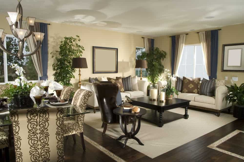 Fresh living room with dark hardwood flooring and white framed windows dressed in multi-colored curtains. It has a leather wingback chair and white sectionals accented with striped, floral and dotted pillows.