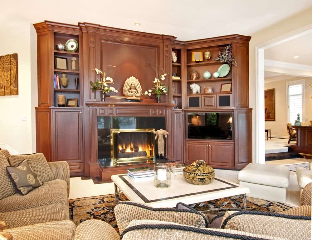 Medium-sized living room decorated with sculptures placed on the built-in cabinet that's fitted with a fireplace. It has comfy sofas and a white coffee table over a floral area rug.