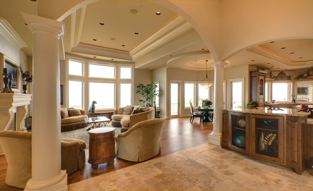 An open living area lined with large columns that form an open archway. It has tan seats and an ornate coffee table facing the fireplace against the beige walls.