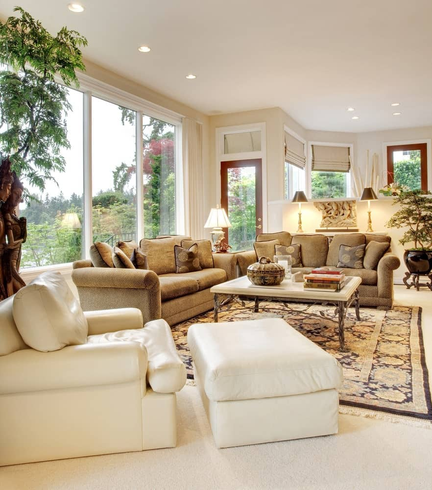 Fresh living room with carpet flooring and glass paneled windows bringing plenty of natural light in. It includes a brown sofa and a white leather lounge chair paired with a matching ottoman.