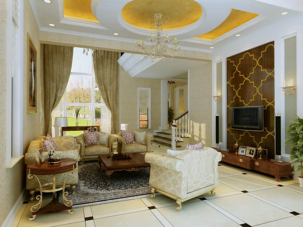 Deluxe living room with tiled flooring and a stunning tray ceiling mounted with recessed lights and a fancy chandelier. It has classy seats and a wall-mount TV fixed on the patterned accent wall.
