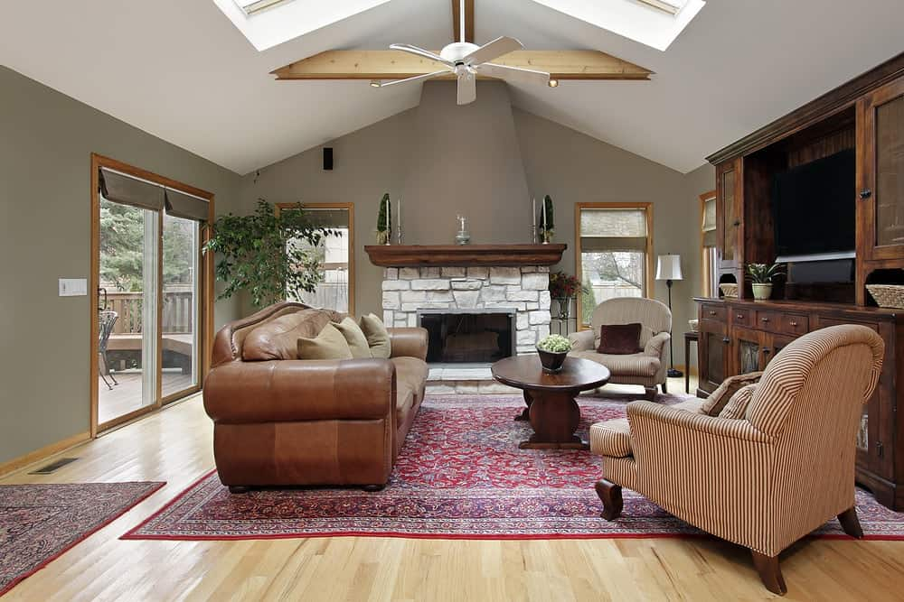 A classic red area rug lays on the light hardwood flooring in this living room with cozy seats and a stone fireplace against the gray wall. It has wooden framed windows and a cathedral ceiling fitted with skylights and a white fan.