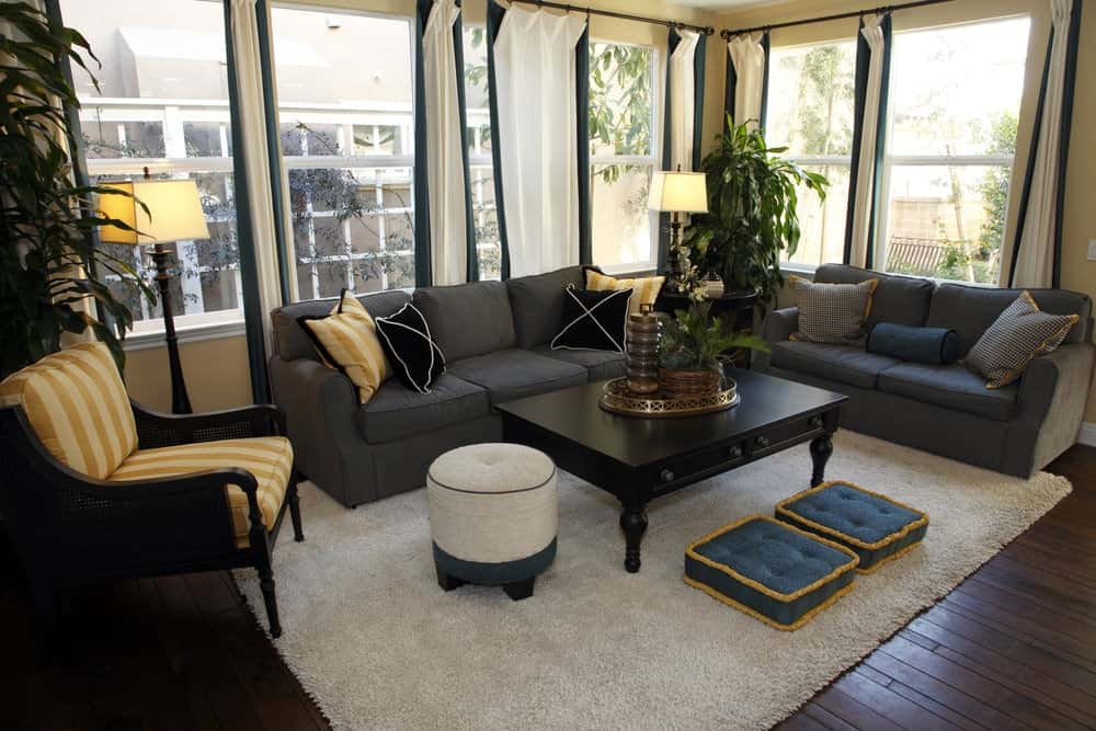 The medium-sized living room offers a black coffee table and gray sectionals accented with black and yellow striped pillows matching with the cushioned armchair. It has glass paneled windows and hardwood flooring topped by a shaggy rug.