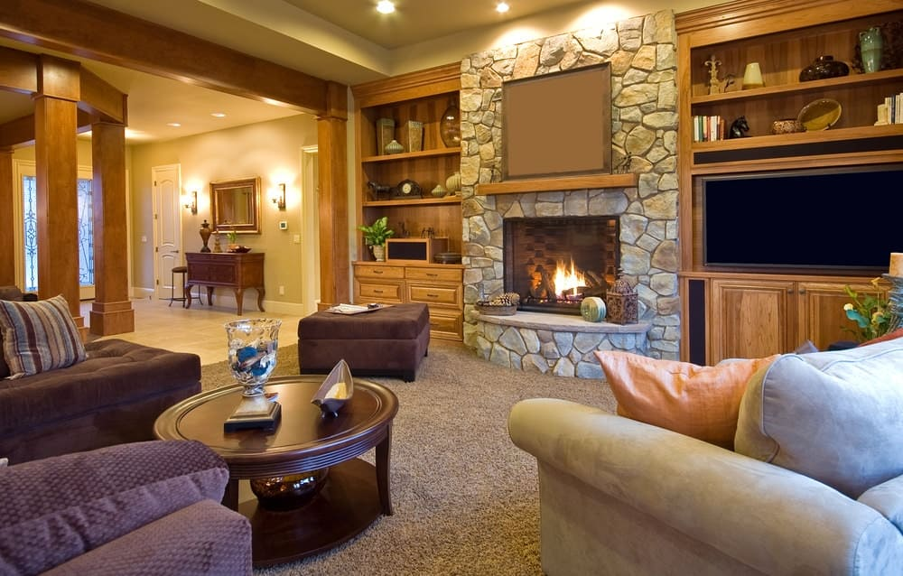 Warm living room with cozy seats and a round coffee table over a beige shaggy rug. It includes a stone fireplace flanked by built-in cabinets and open shelvings.