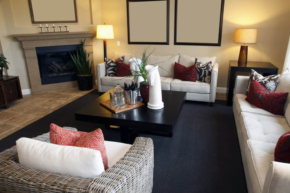 The fresh living room features a wicker armchair and beige tufted sectionals accented with black and red patterned pillows. It includes a black coffee table and a corner fireplace topped with an iron candle holder.