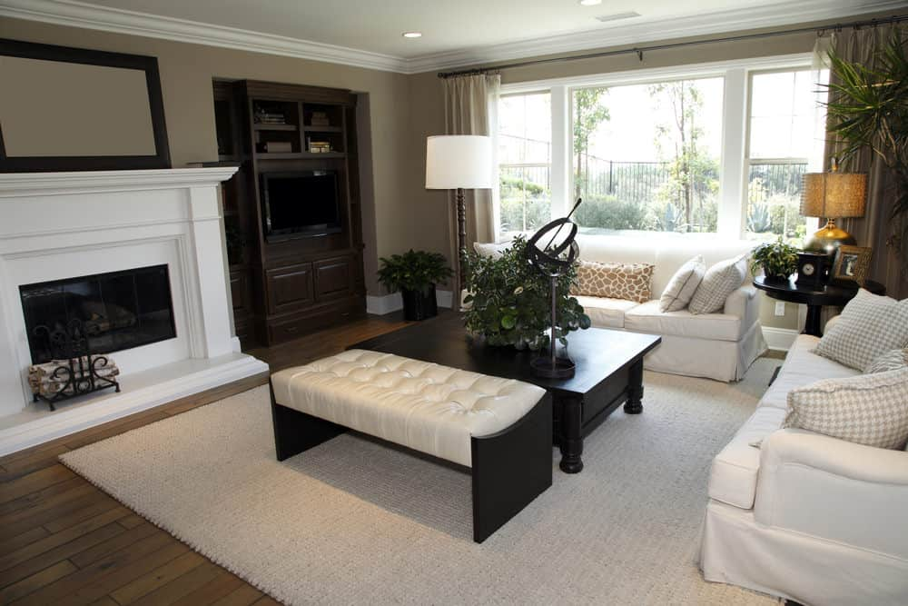 A white tufted ottoman sits beside the black coffee table paired with white skirted sofas. There's a fireplace next to the built-in cabinet situated on the inset wall.