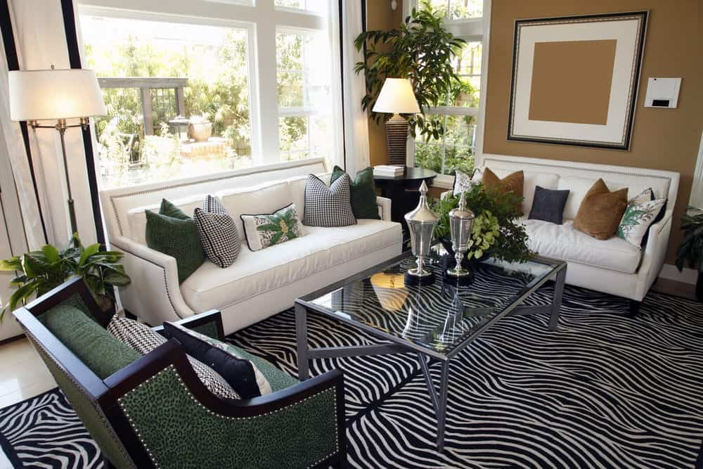 Airy living room with white leather sofas and a green armchair paired with a glass top coffee table that sits on a zebra area rug. It is illuminated by a drum floor lamp and a table lamp along with natural light from the glazed windows.
