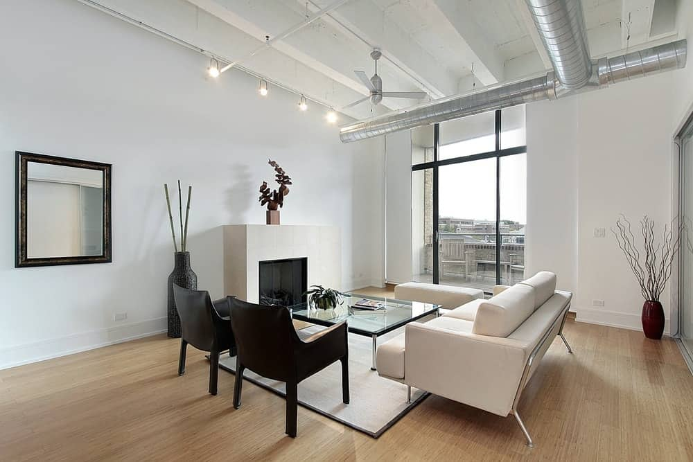 Industrial living room boasts white sectional and bench contrasted by black armchairs. It has smooth hardwood flooring and a beamed ceiling lined with exposed pipes.