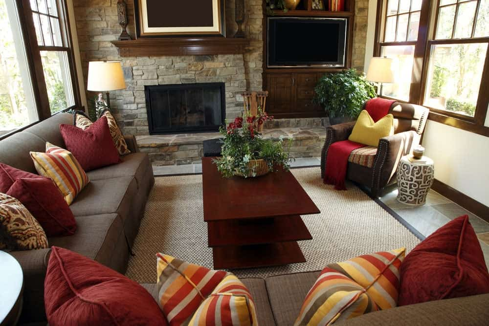 Fresh living room with a TV and fireplace fitted on the stone brick wall. It includes a wooden coffee table and sectional sofas accented with red and multi-colored striped pillows.