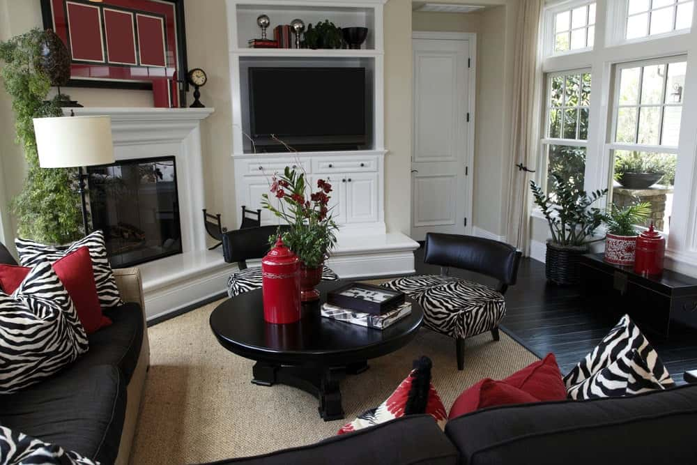 A corner fireplace sits next to the TV placed on the white cabinet. This room features a round coffee table and black sectional filled with red and zebra pillows that complement the cushioned chairs.