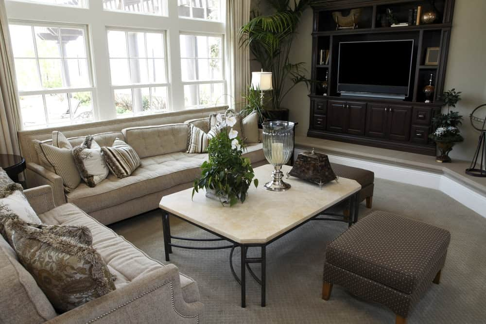 Medium-sized living room with carpet flooring and beige walls dominated by large white framed windows. It includes classy sofas and dotted ottomans surrounding a metal coffee table topped with a potted plant and glass candle holder.