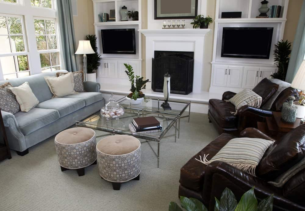 White built-in cabinets flank a fireplace enclosed in an iron three-panel fence. It faces the glass top coffee tables and round ottomans with blue sectional sofa and leather armchairs on the sides.