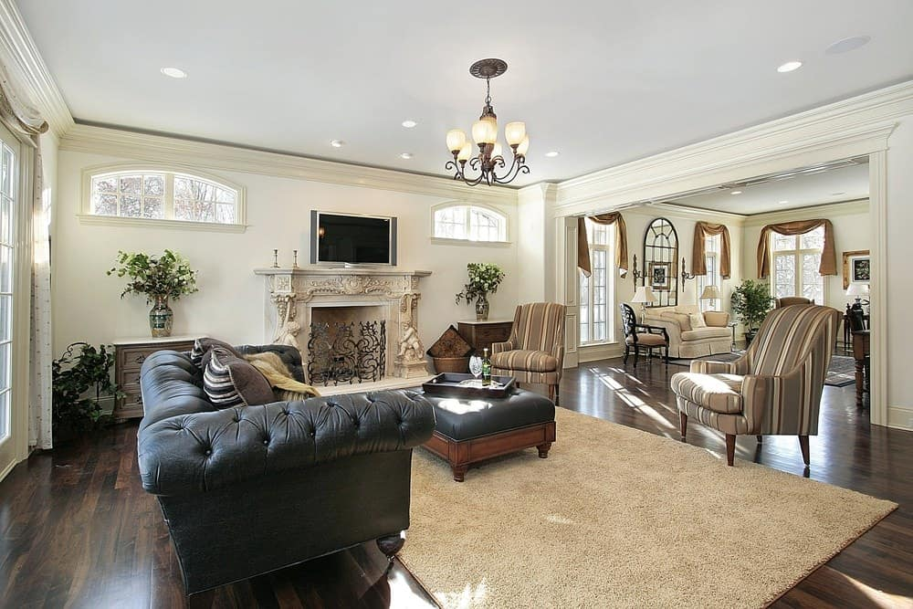 An ornate chandelier illuminates this living room showcasing striped armchairs and a black leather sofa that complements the tufted ottoman over a beige shaggy rug. It includes a TV fixed above the fireplace inlaid with floral and cherubs sculptures.
