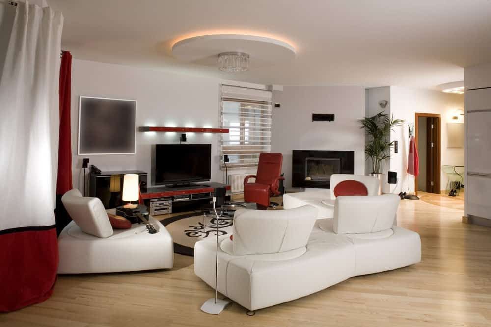 The modern living room offers white couches and red armchair surrounding a glass top coffee table illuminated by a round lighting fixture. It includes a flat-screen TV and fireplace with a tall potted plant on the side.