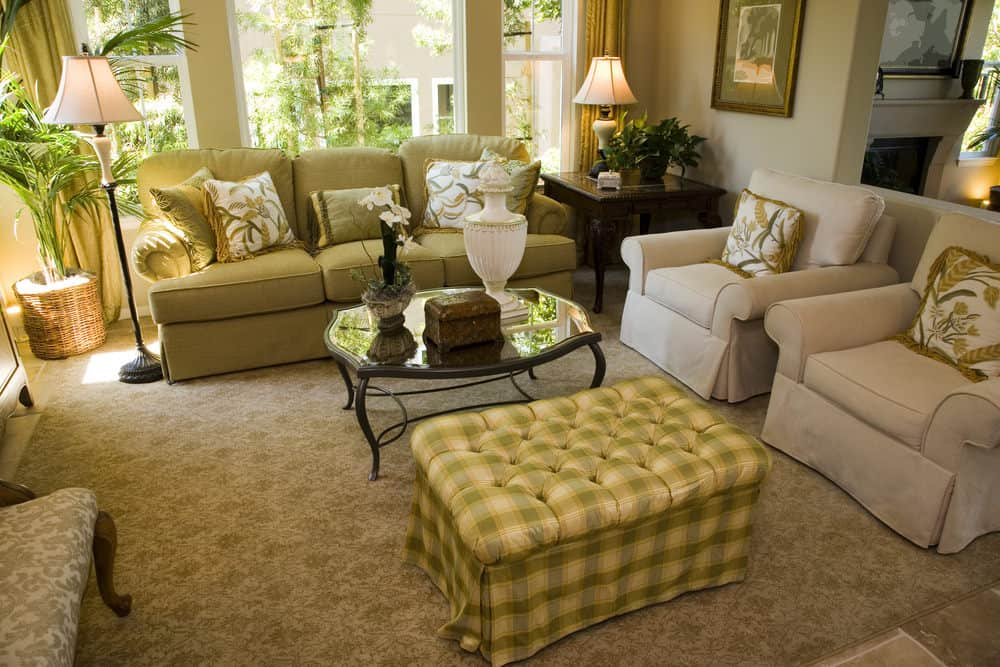 Airy living room with beige skirted chairs and a green sectional sofa facing the metal coffee table and plaid tufted ottoman over a patterned area rug. It has limestone flooring and large glazed windows bringing plenty of natural light in.
