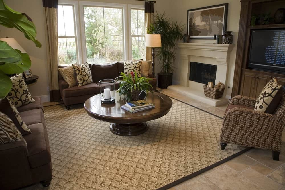 Brown sectionals and a wicker armchair surround a wooden coffee table that sits on a patterned area rug, It is accompanied by a built-in cabinet and a fireplace with lovely artwork on top.