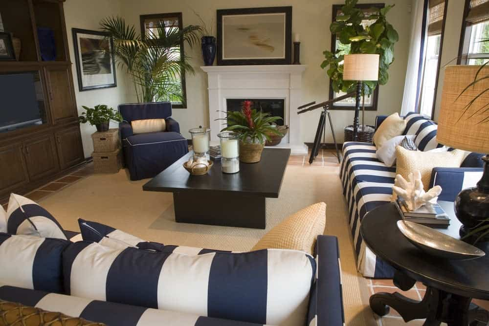 This living room offers nautical seats and a dark wood coffee table over a jute rug. it includes black framed artworks and a fireplace along with a TV placed on the built-in cabinet.