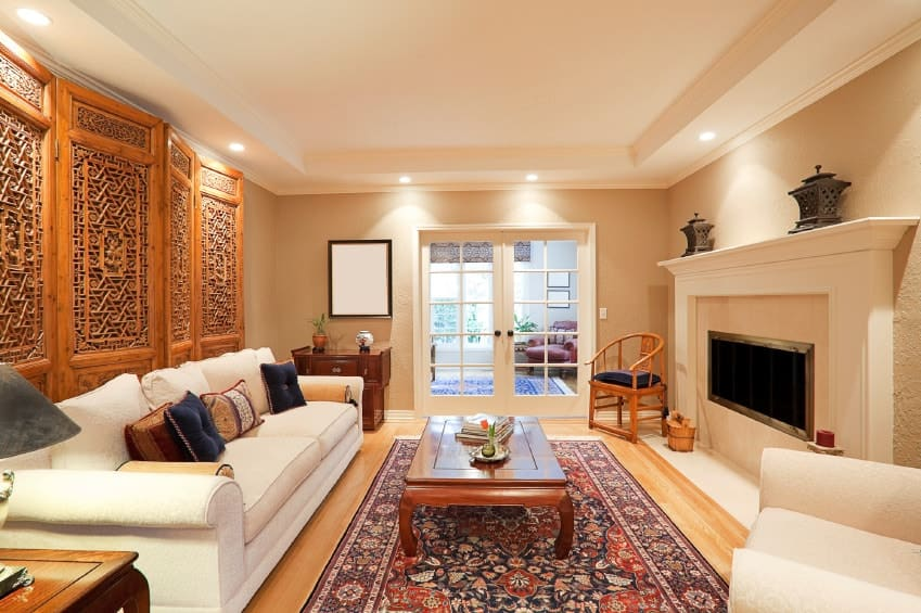 Ambient light from the recessed ceiling lights creates a warm and cozy feel in this living room with white seats and a wooden coffee table on a floral area rug facing the fireplace against the beige wall.