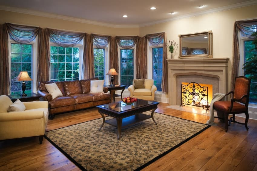 A warm living room surrounded with framed windows dressed in sheer valances. It has cozy seats and a dark wood coffee table over a floral area rug facing the fireplace enclosed in an ornate iron screen.
