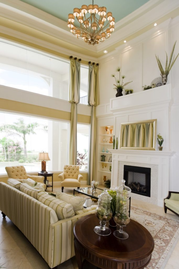 A gorgeous artwork above the fireplace complements the striped sofa and draperies covering the panoramic windows. It is illuminated by recessed lights and a Victorian chandelier that hung from the high tray ceiling.