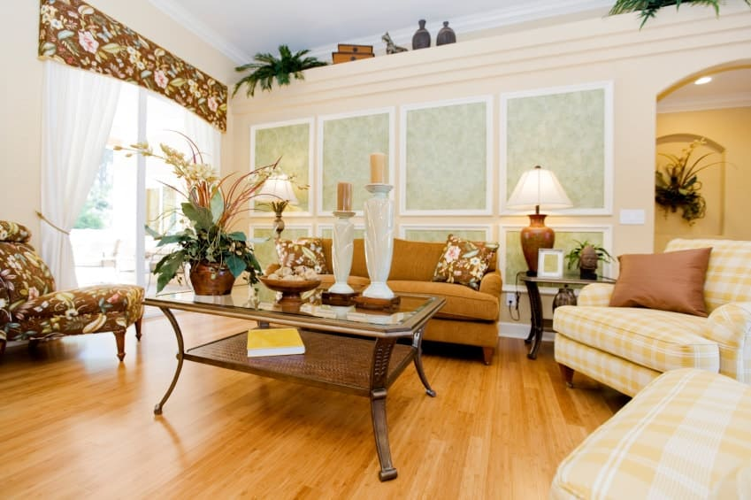 The charming living room showcases wainscoted wall and full height glazing covered in white drapes and floral valance that matches the pillows and lounge chair. It includes a brown sofa and yellow plaid armchairs paired with a glass top coffee table over the rich hardwood flooring.