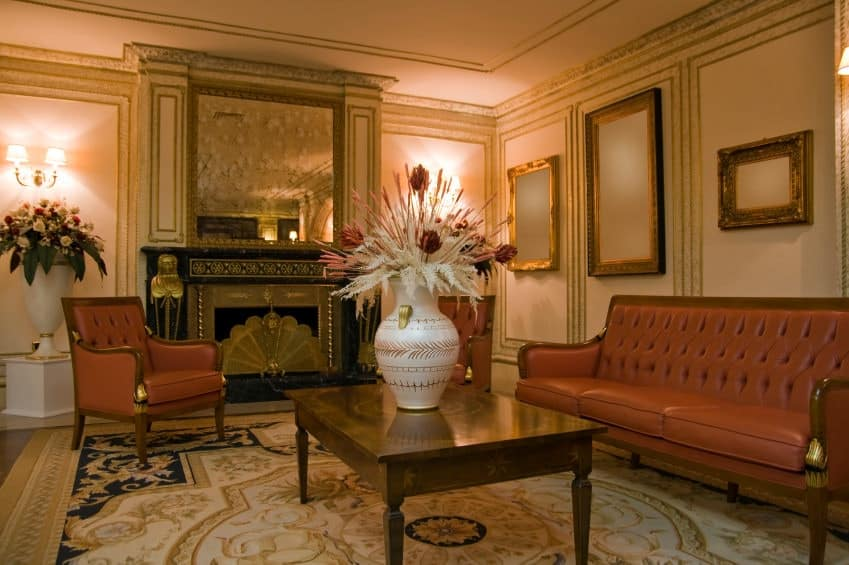 The classy living room offers red tufted seats and a wooden coffee table on a chic area rug facing the gorgeous fireplace that's topped with a brass framed mirror. It has a tray ceiling and wainscoted walls mounted with elegant wall arts and sconces.