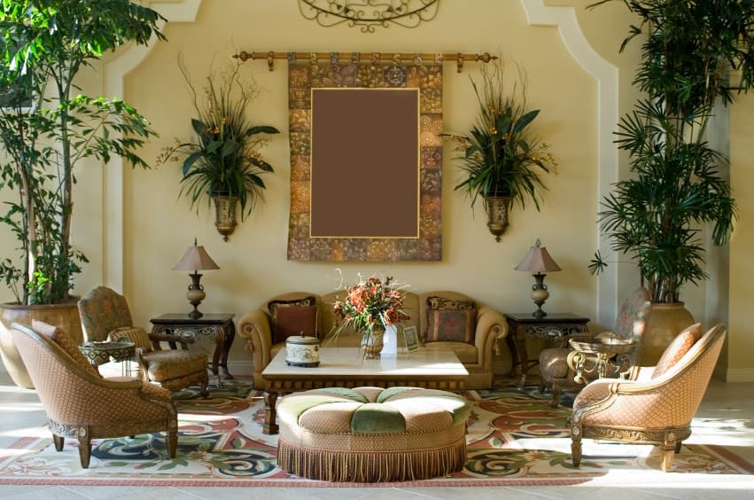 Tropical living room decorated with potted plants and a gorgeous bordered tapestry that hung above the sectional sofa accompanied by classy chairs and a wooden coffee table with a round ottoman on the side.