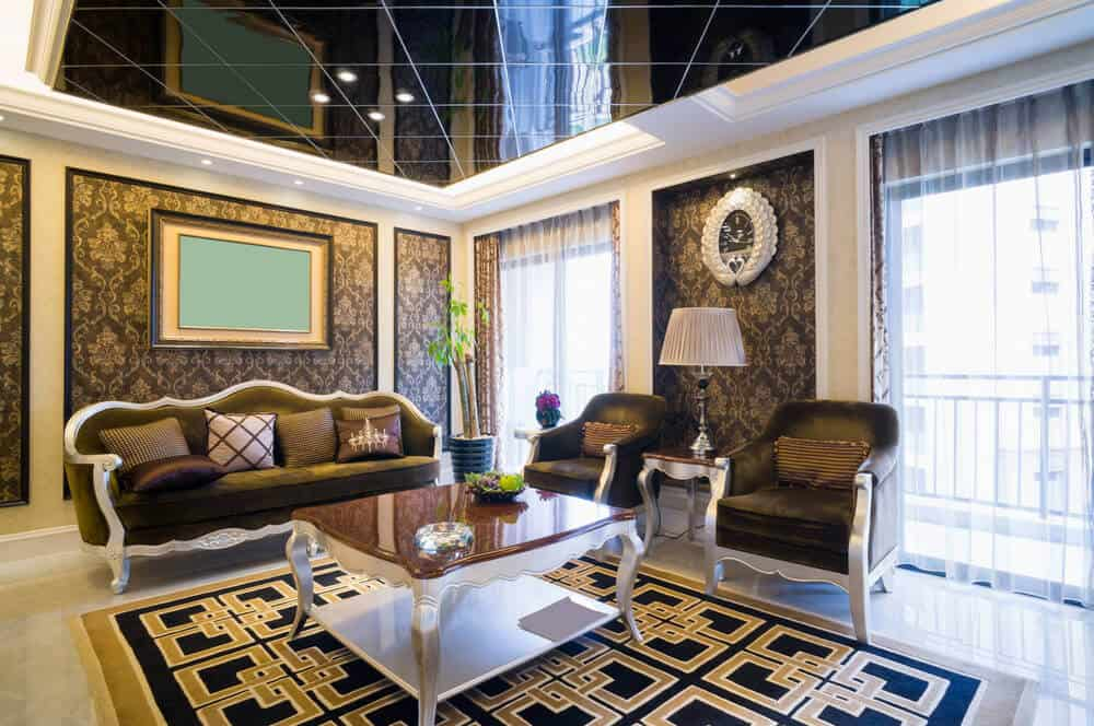 Luxury living room designed with mirrored ceiling and full height wainscoting clad in classy wallpaper. It has elegant seats and a coffee table on an eye-catching rug over marble flooring.