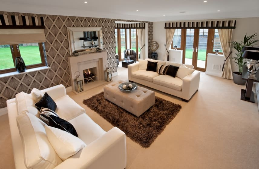 Clad in diamond-patterned wallpaper, this living room features facing white couches with a tufted ottoman in the middle that sits on a brown shaggy rug. It has carpet flooring and wooden framed windows dressed in striped valances and beige draperies.