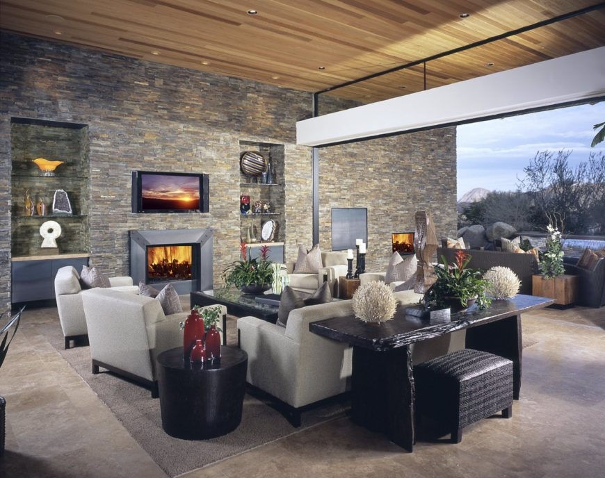 Medium-sized living room with limestone flooring and brick wall fitted with inset niches that are fixed with glass shelves. It includes a fireplace and gray seats paired with a black coffee table.