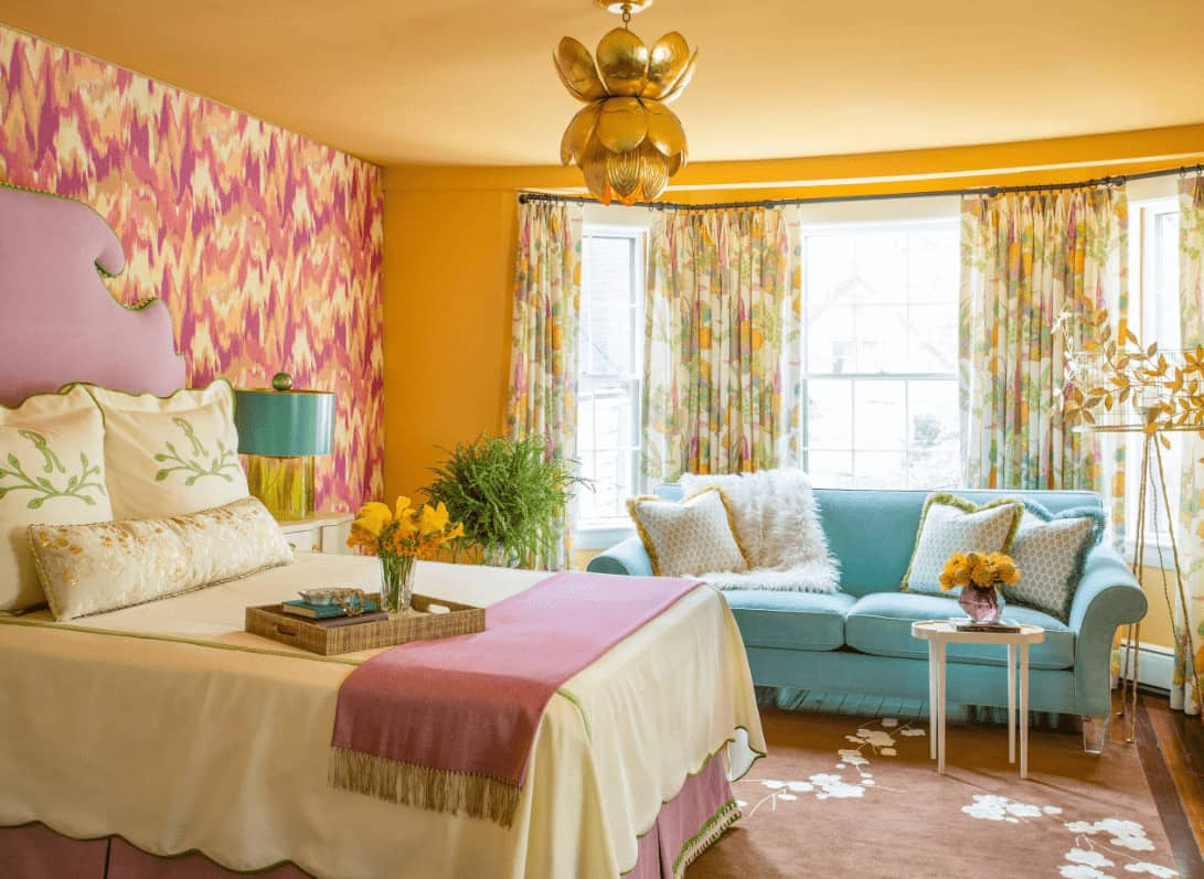 Charming bedroom showcases a pink skirted bed and blue sectional sofa filled with fluffy pillows. It is illuminated by a gold chandelier along with natural light that flows in through the bay window. pink skirted bed and blue sectional sofa filled with fluffy pillows. It is illuminated by a gold chandelier along with natural light that flows in through the bay window.