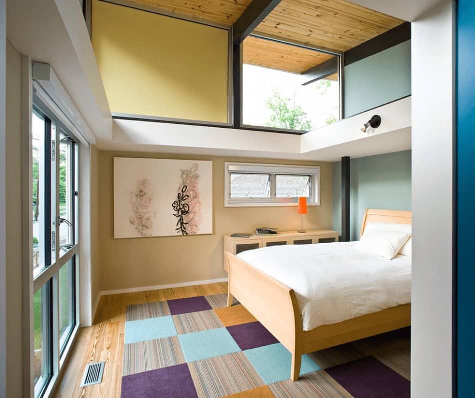 Contemporary bedroom with multi-colored walls and glass paneled windows allowing natural light in. It has lovely artwork and a light wood bed that sits on a checkered area rug.
