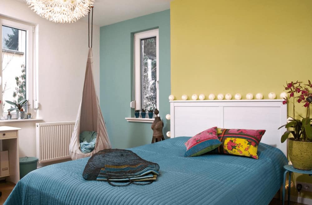 A lovely potted plant sits next to the white bed dressed in teal bedding in this multi-colored bedroom boasting a fabric hanging chair and glazed windows that invite natural light in.