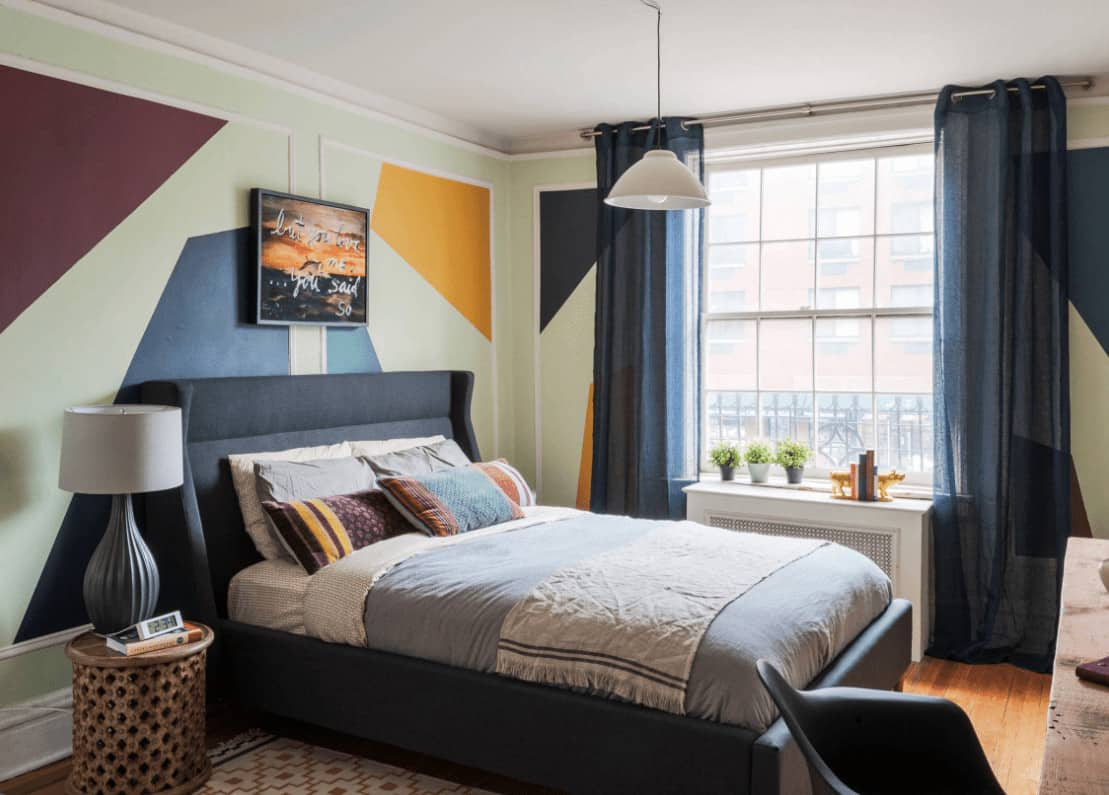 A bachelor pad with a white framed window and wainscoted walls painted in geometric design. It has a white dome pendant and navy blue bed paired with a round nightstand.