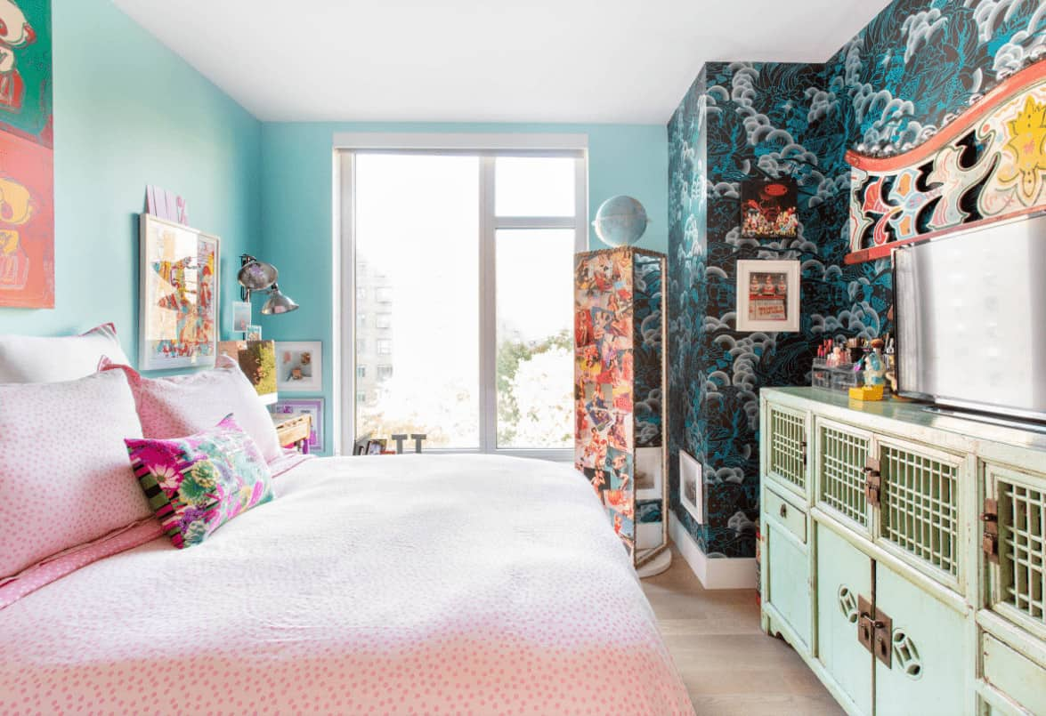 This bedroom showcases a rotating full length mirror and pink dotted bed facing the distressed green cabinet. It includes colorful artworks mounted on the aqua walls.