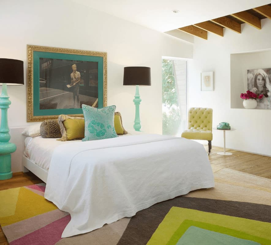 A tufted yellow green chair sits next to the white bed flanked by aqua floor lamps. This room has gorgeous framed photos and a striking printed rug that lays on the natural hardwood flooring.