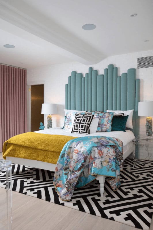 A blue floral throw blanket lays on the stylish bed in this primary bedroom with an eye-catching patterned rug and blush pink drapes covering the glazed windows.