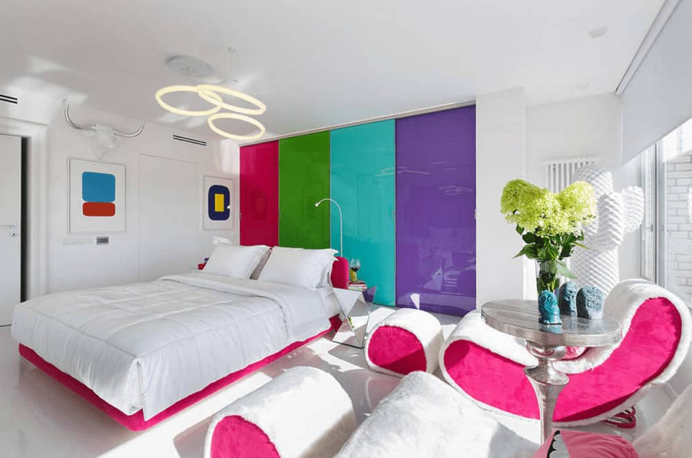 Stylish bedroom boasts white furniture with pink accents along with a built-in wardrobe fitted with multi-colored doors. It is illuminated by round pendant lights that hung over the platform bed.