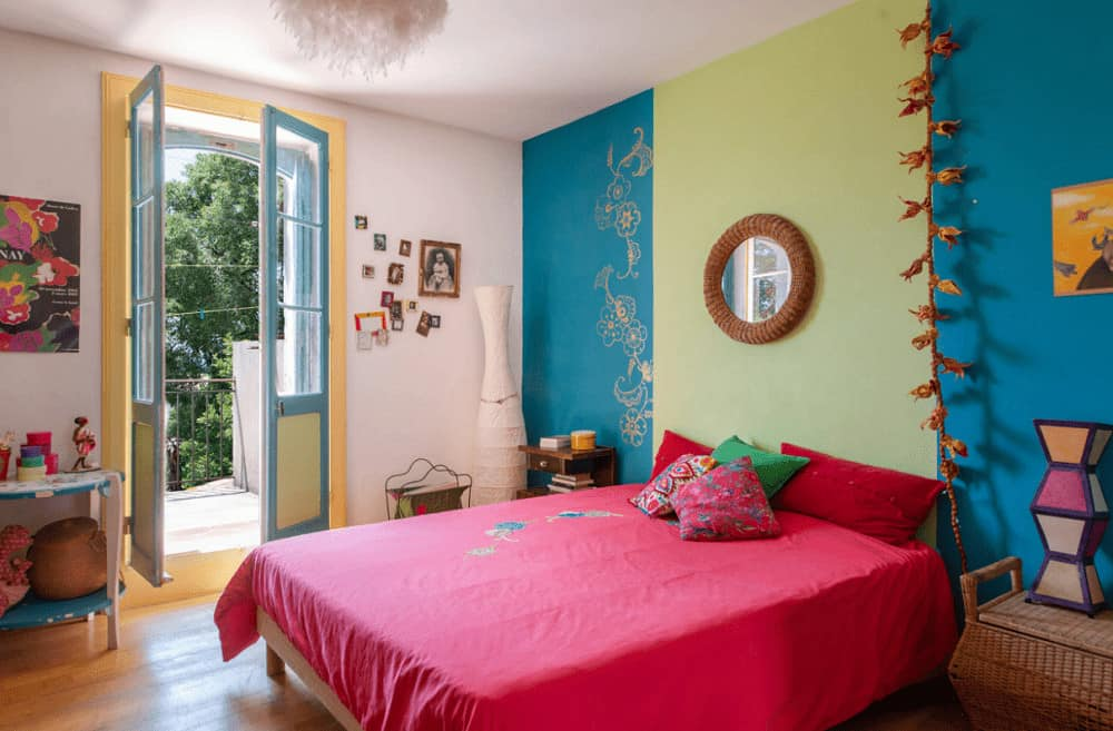 Multi-colored bedroom with hardwood flooring and a French door that opens to the balcony. It includes a round mirror and a comfy bed wrapped in a red blanket.