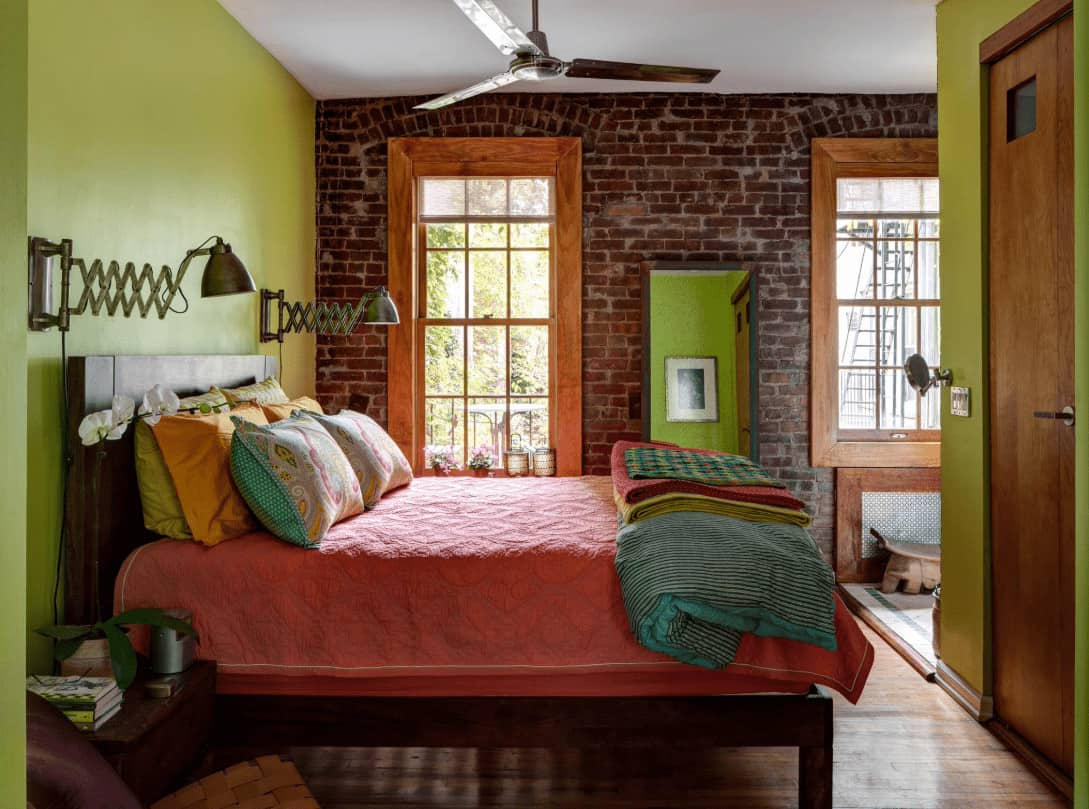 A red brick accent wall adds texture in this multi-colored bedroom showcasing a wooden bed and chrome sconces mounted on the green wall.