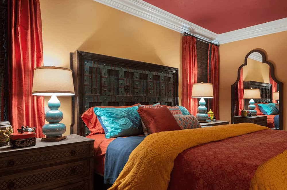 Mediterranean bedroom with red ceiling and orange walls lined with white crown molding. It has an arched mirror and carved wood bed lighted by stylish table lamps.