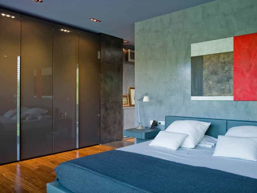 Modern primary bedroom with high gloss gray wardrobes and a blue leather bed paired with a built-in nightstand. It is decorated with a sleek artwork mounted on the concrete wall.