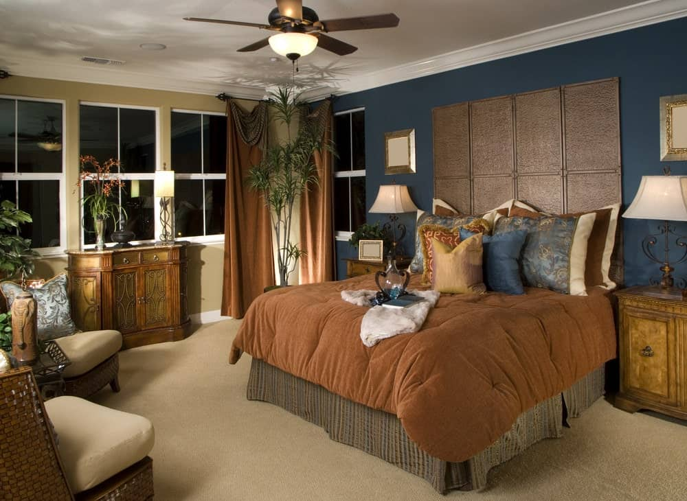 Multi-colored primary bedroom with a carved wood console table and a skirted bed placed against the taupe and deep blue walls. It is accompanied by wicker chairs and wooden nightstands topped with ornate table lamps.