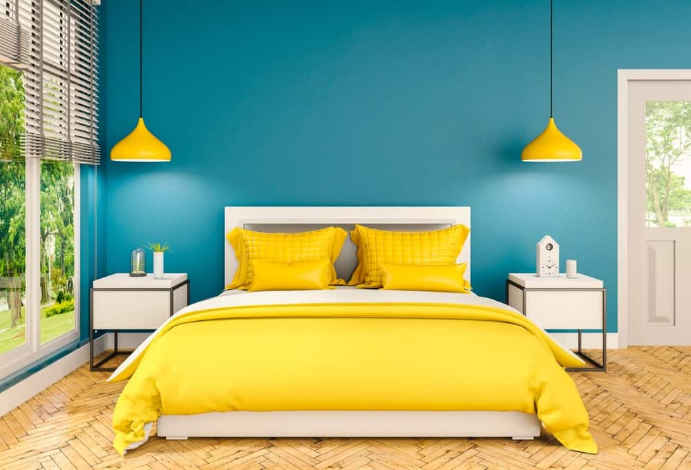 Primary bedroom with blue and yellow color scheme showcasing dome pendant lights and a white bed in between sleek nightstands. It has herringbone wood flooring and glass paneled windows covered in roller blinds.