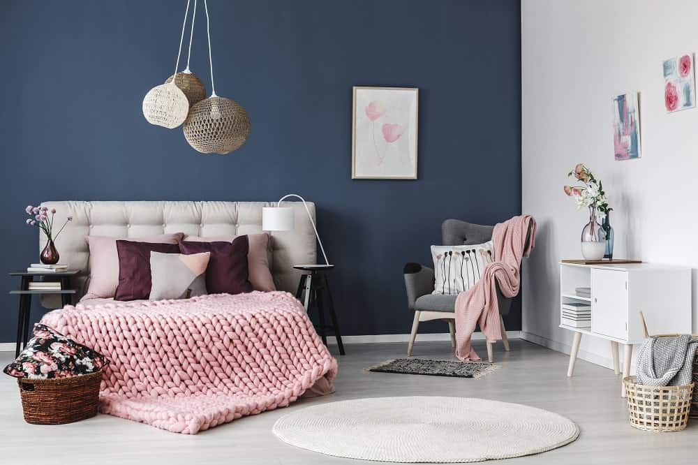 This primary bedroom boasts boho pendant lights and a tufted bed wrapped in a pink knitted blanket. It is accompanied by a gray wingback chair and a white console table topped with translucent vases.